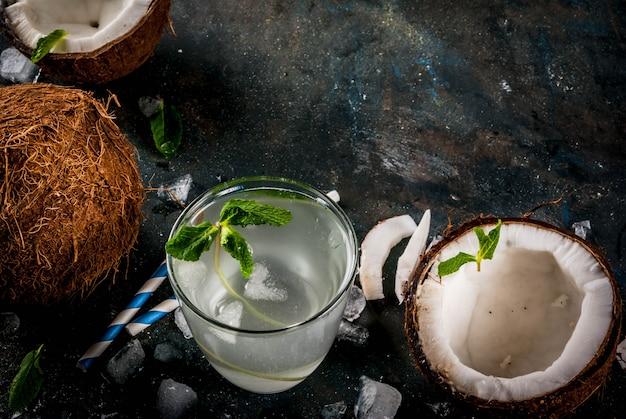Concetto sano dell'alimento acqua di cocco organica fresca con i cubetti di ghiaccio e la menta delle noci di cocco su fondo blu scuro arrugginito