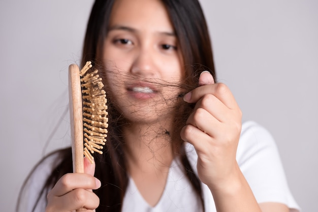 Concetto sano. la donna mostra la sua spazzola con i capelli danneggiati a perdita lunga