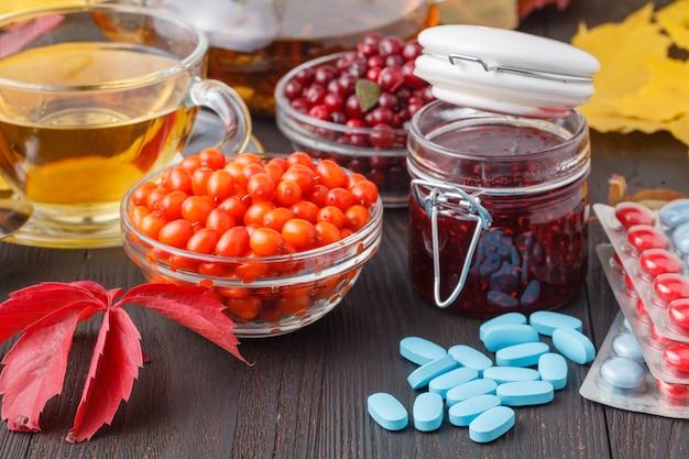 Concetto sano. tè della bacca di inverno con i mirtilli rossi, il miele e il timo in una tazza di vetro sulla tavola di legno. alternativo alla medicina tradizionale