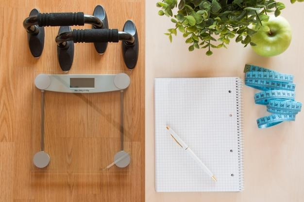 Concetto, scala e taccuino di perdita di peso e di forma fisica su una tavola di legno, vista superiore