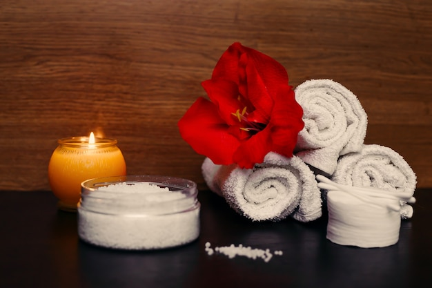Concetto spa. candela accesa, asciugamani bianchi, fiori e sale. sfondo scuro.