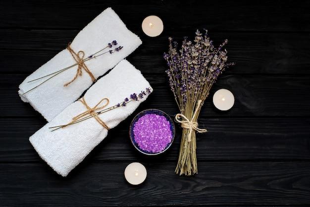 Concetto spa. sale di lavanda per un bagno rilassante, candele, asciugamani bianchi e fiori secchi di lavanda su un fondo di legno nero. aromaterapia piatto disteso.