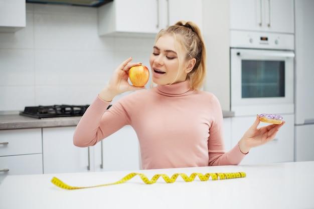 Concetto stante a dieta, bella giovane donna che sceglie fra alimento sano e alimenti industriali