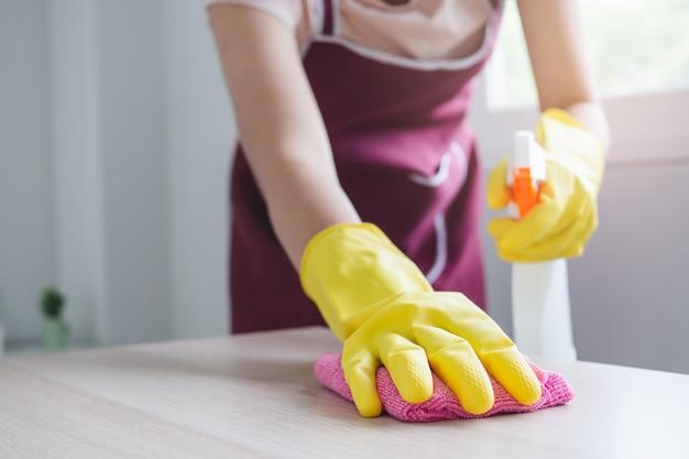 Concetto un giorno di attività casalinga a casa. primo piano vista persona utilizzando un panno in microfibra spazzare la polvere sul tavolo.