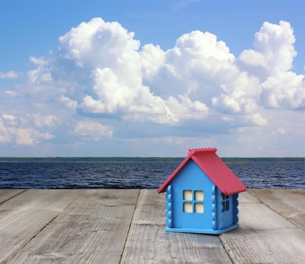 Concetto: una piccola casa di legno blu sul mare.
