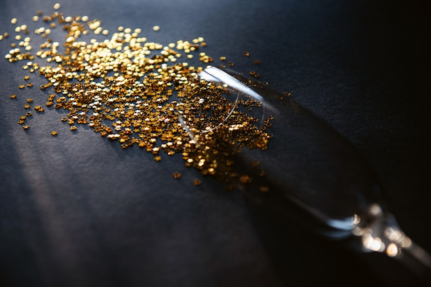 Concetto versato vino bianco o champagne. fine della festa. un bicchiere di vino adagiato su un tavolo con stelle dorate che simboleggiano il vino versato