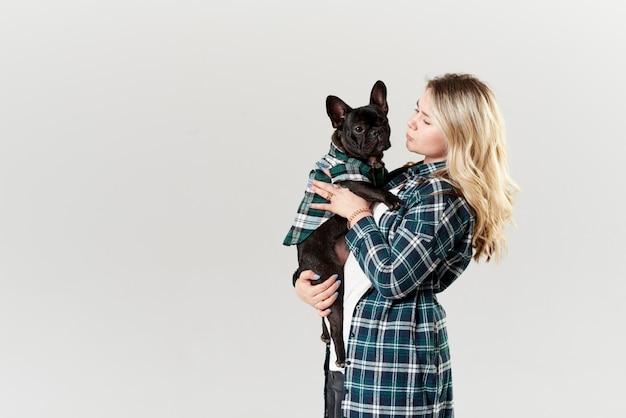 Concetto veterinario. donna felice dei pantaloni a vita bassa che gioca con il bulldog francese sulla parete bianca