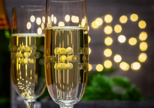 Concetto-vetro della decorazione del nuovo anno di champagne sul fondo vago del nuovo anno