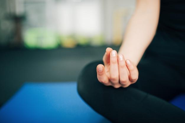 Concetto zen primo piano della persona di sesso femminile nella posizione del loto, messa a fuoco sulla mano.