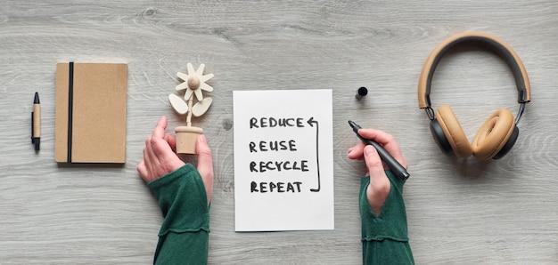 Concetto zero consumo consapevole dei rifiuti disteso. immagine panoramica, vista dall'alto di mani che tengono un fiore di legno, taccuino di fustagno con copertina in cartone artigianale, occhiali da lettura e auricolari su legno.