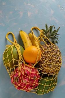 Concetto zero rifiuti, borsa in tessuto a rete con frutti tropicali freschi: mango, ananas, drago, kiwi, banana, frutto della passione su superficie blu chiaro, orientamento verticale