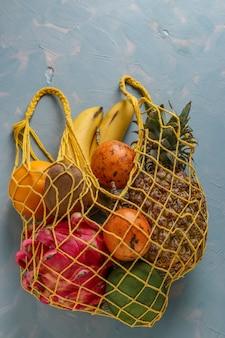 Concetto zero rifiuti, borsa in tessuto a rete con frutti tropicali freschi