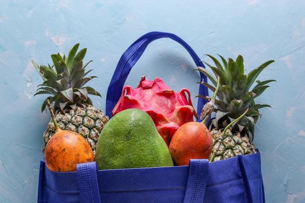 Concetto zero rifiuti, borsa shopping in tessuto blu con frutti tropicali freschi: mango, ananas, drago e frutto della passione