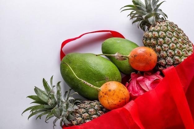 Concetto zero rifiuti, borsa shopping in tessuto rosso con frutti tropicali freschi: mango, ananas, drago e frutto della passione sulla superficie bianca