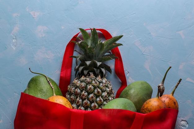 Concetto zero rifiuti, borsa shopping in tessuto rosso con frutti tropicali freschi: mango, ananas e frutto della passione sulla superficie blu chiaro