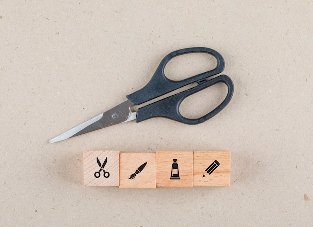 Concettuale di artigianato con blocchi di legno con icone, forbici laici piatta.