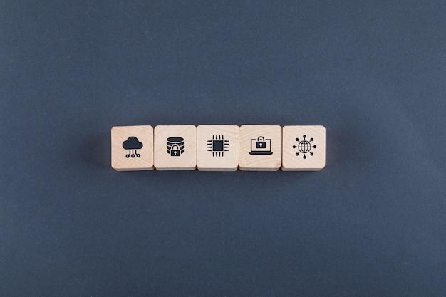 Concettuale di cloud server e business. con blocchi di legno con icone sulla tavola di colore scuro piatto laici.
