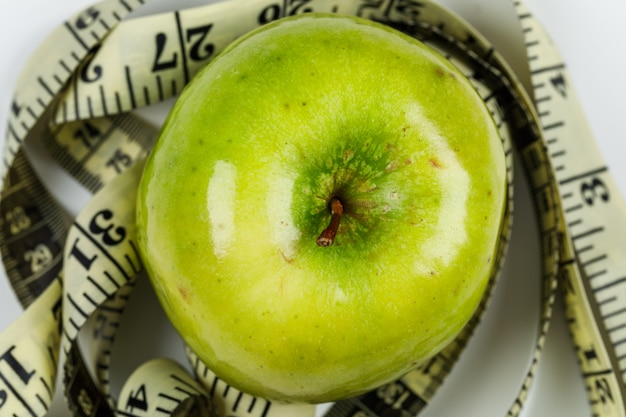 Concettuale di dieta e mela. con metro su piano tavolo bianco. immagine orizzontale