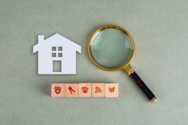 Concettuale di ricerca immobiliare con blocchi di legno, icona domestica di carta e lente di ingrandimento.