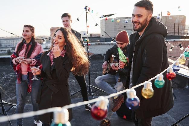 Concezione del partito. le lampadine in tutto il luogo sul tetto dove è giovane gruppo di amici hanno deciso di trascorrere il loro fine settimana con chitarra e alcool