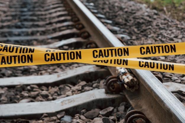 Concezione del terrorismo. esplosivo pericoloso che giace sulla ferrovia. nastro giallo di avvertenza davanti