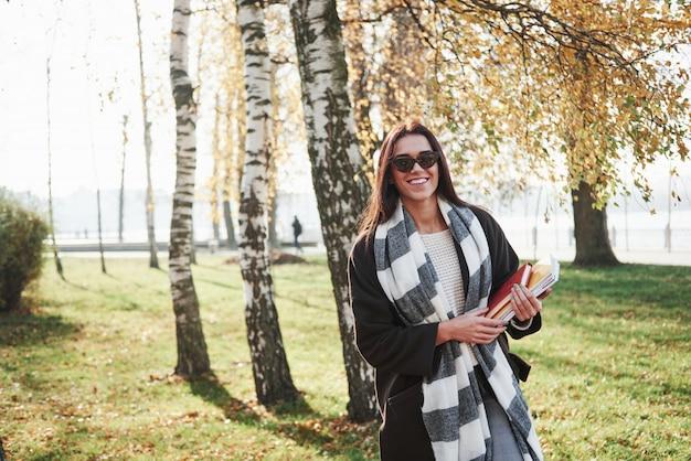Concezione di studio e riposo. il giovane castana sorridente in occhiali da sole sta nel parco vicino agli alberi e tiene il blocco note