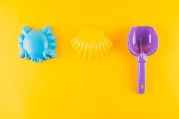 Conchiglia di capesante di plastica blu; granchio e pala di plastica su sfondo giallo