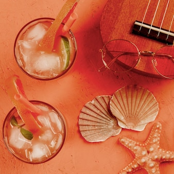 Conchiglia; ukulele; occhiali e bicchieri di succo con cannuccia su sfondo con texture