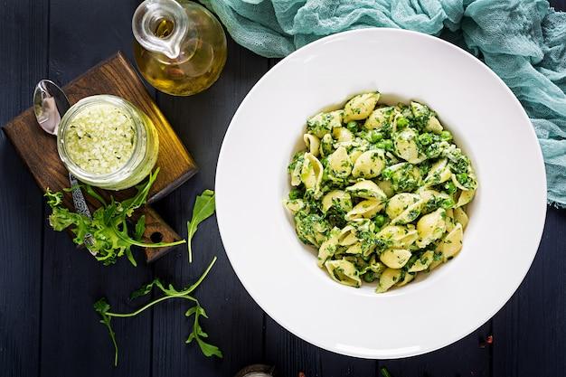 Conchiglie agli spinaci e pesto di piselli. cucina italiana. cibo vegano. vista dall'alto