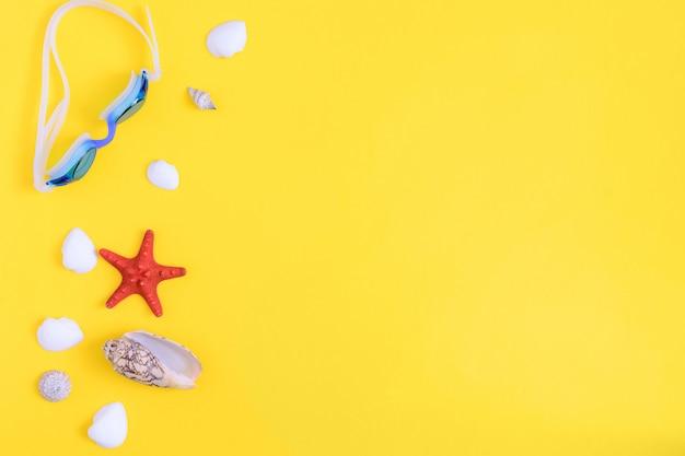 Conchiglie diverse, una stella marina rossa e bicchieri per nuotare sul giallo