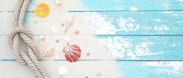 Conchiglie e corda sulla sabbia su assi di legno blu