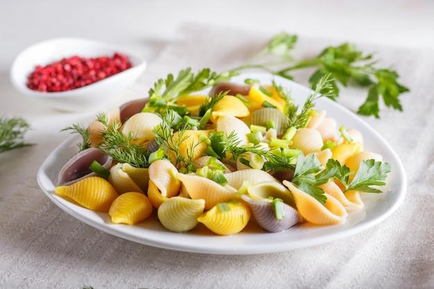 Conchiglie ha colorato la pasta con greengrocery fresco su una tovaglia di tela su fondo di legno bianco.