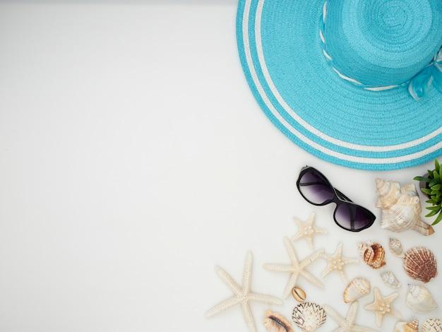 Conchiglie, stelle marine, cappelli di paglia, occhiali da sole su uno sfondo bianco