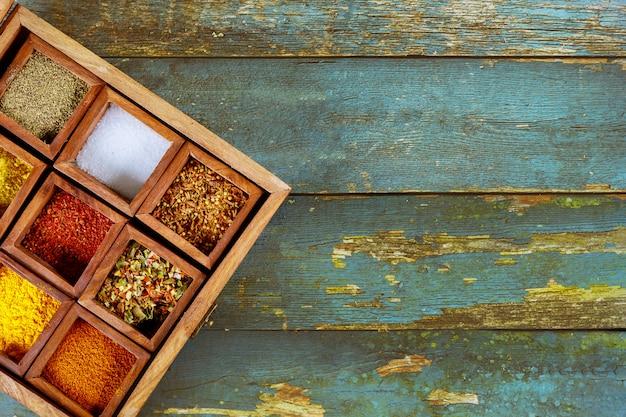 Condimento delle varie spezie piccante nella vista superiore della scatola di legno