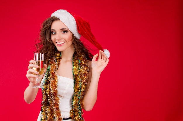 Condimento femminile sorridente felice delle giovani belle donne che indossa champagne leggiadramente bevente della canutiglia del cappello bianco di santa claus christmas del cappello che celebra il nuovo anno di vacanze invernali