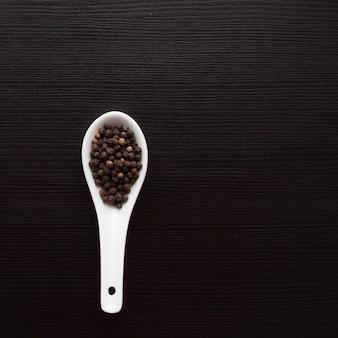 Condimento in cucchiaio bianco sul tavolo nero. cucinando. copia spazio
