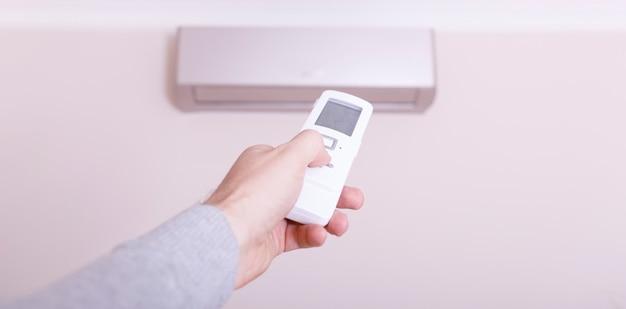 Condizionatore d'aria che soffia aria calda. mano con telecomando diretto sul condizionatore.