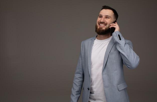 Condizione d'uso del vestito barbuto bello dell'uomo di affari isolata sopra la parete grigia, facendo uso del telefono cellulare