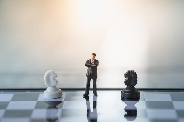 Condizione della miniatura dell'uomo d'affari sulla scacchiera con gli scacchi in bianco e nero del cavaliere