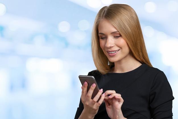 Condizione sorridente della donna di affari e telefono cellulare usando