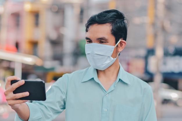 Conferenza asiatica di videochiamata della maschera di protezione di uso dell'uomo sulla via nel nuovo concetto di distanziamento sociale normale della città