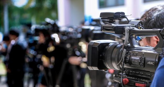 Conferenza stampa primo piano della videocamera sul gruppo sfocato di stampa e fotografo multimediale