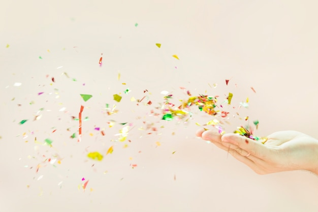 Confetti che soffia dalle mani su sfondo beige