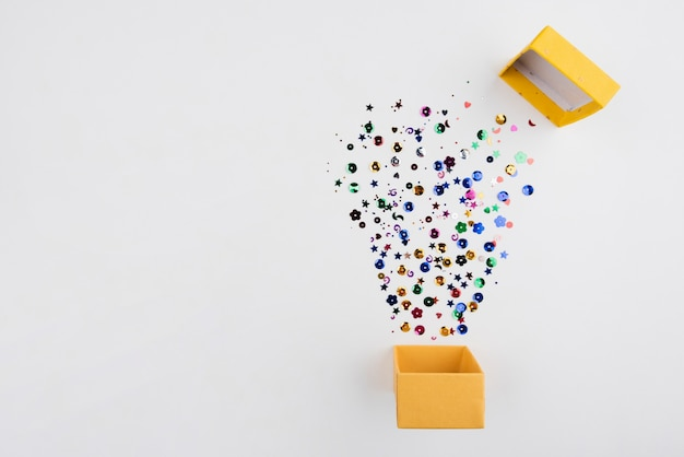 Confetti saltar fuori dalla scatola con copia-spazio