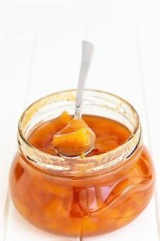 Confettura casalinga della marmellata della pesca o della nettarina in barattolo e cucchiaio di vetro su bianco
