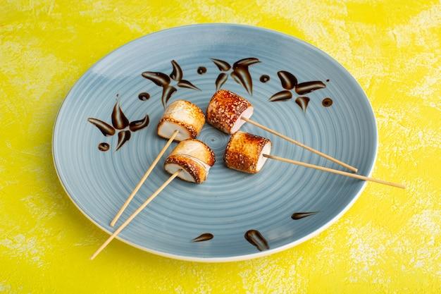 Confettura di bastoncini all'interno del piatto blu su giallo
