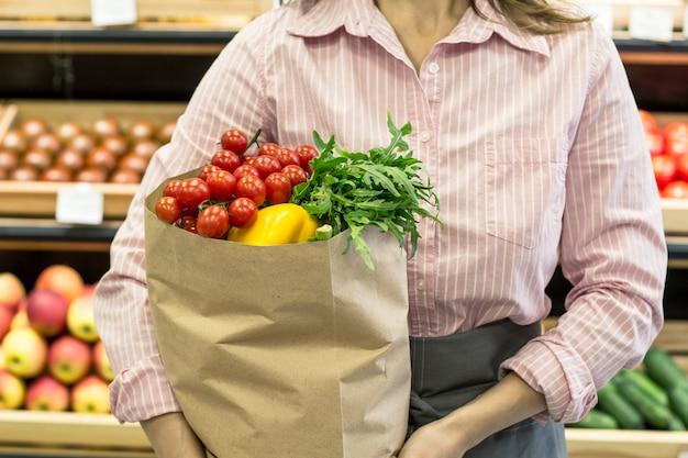 Confezione con prodotti, verdure, nelle mani di una donna.