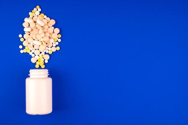 Confezione con un mucchio di pillole mediche su sfondo blu