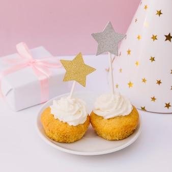 Confezione regalo avvolta; cappello di partito e cupcake con stella d'oro e d'argento sulla scrivania bianca