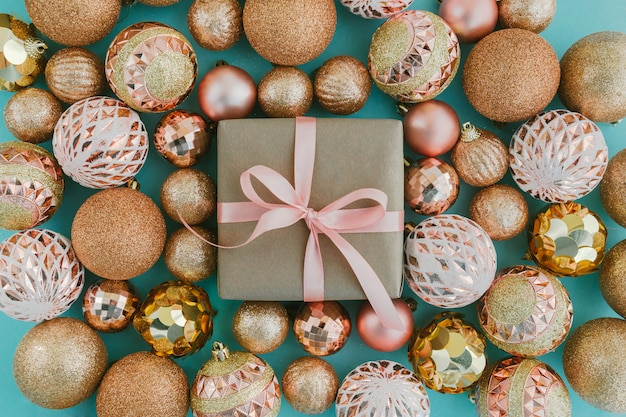 Confezione regalo avvolto in carta artigianale con nastro rosa e sfere dorate dell'albero di natale su sfondo azzurro con glitter.